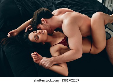 Passionate couple having sex on black bed. Hot brunette woman and handsome muscular man in bedroom.