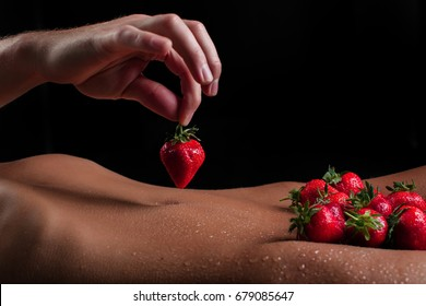 Passionate couple kissing, boy and girl. Having sex. Young lovers. People in love. Positions kamasutra. Erotic moments. Concept photo. Secret. Fashion. Hot babe. Party. Night background. Strawberries.
