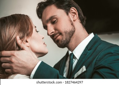 Passionate couple looks at each other. Love affair in office. Caucasian man in a business suit touches a woman by the neck and hair.