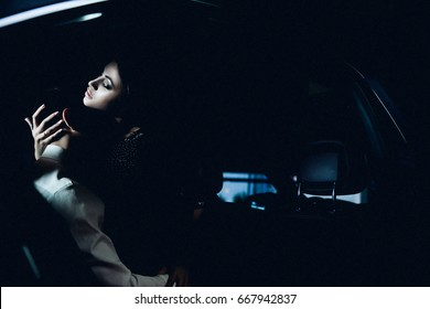 Passionate couple man and woman in the car salon.sexy. love. hug. feelings emotions. in the back seat. copy space. black background. dark photo.night