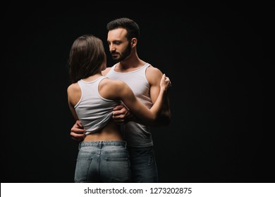 passionate couple in white singlets and jeans isolated on black
