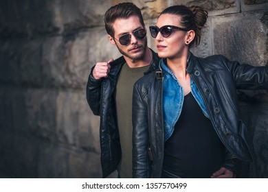 Passionate and cute young couple hugging and kissing in a dark corner of the city street