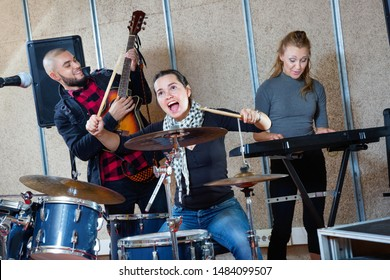 Passionate emotional happy cheerful positive smiling female drummer with her bandmates practicing in rehearsal room