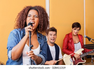 Passionate female singer performing with band members in recording studio