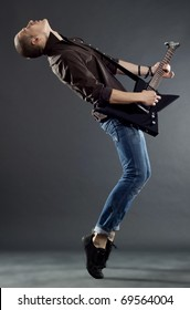 Passionate guitar player, playing his guitar on his tip toes