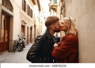 Passionate kiss between fashionable man and cute woman on first date. Portrait of attractive European guy kissing his beautiful girlfriend on her lips after nice walk on streets of European town