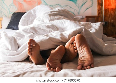 Passionate love. Feet of a young couple that lying on the bed at honeymoon. Couple in love having sex / Lovers having sex under blanket. Concept : love, sex, sweetheart, sweet, activity, lifestyle.