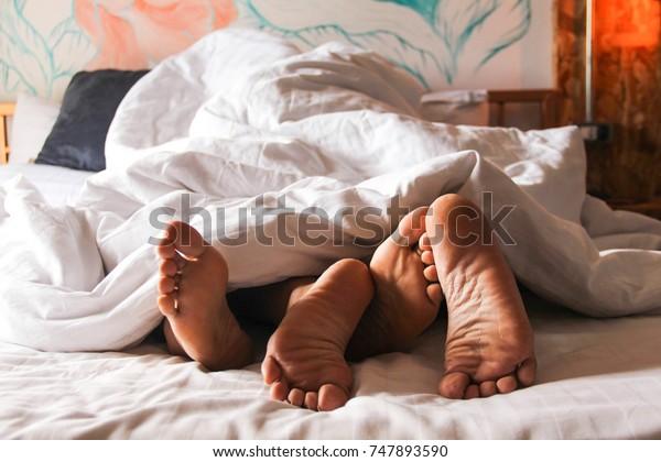 情熱的な愛。新婚旅行でベッドに寝転がった若い夫婦の足。セックスを好むカップル/毛布の下でセックスをする恋人。コンセプト:愛、セックス、恋人、甘い、活動、ライフスタイル。