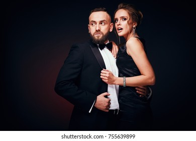 Passionate luxury couple: handsome bearded man in tuxedo with amazing woman with blonde updo hair, wearing silky black dress and chic jewelry, posing in dark studio