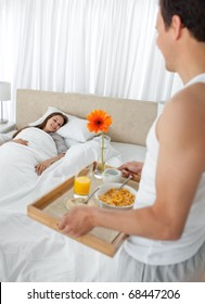 Passionate man bringing the breakfast to his girlfriend in the bedroom at home