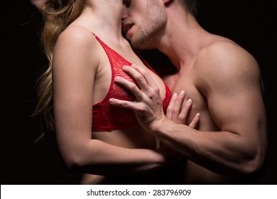 Passionate man kissing woman in red lingerie