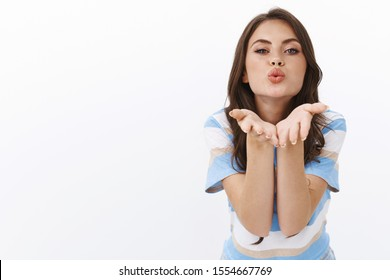 Passionate sensual good-looking modern caucasian woman lean camera to kiss, blowing air muah holding hands near pouted lips to send flirty message, stand white background romantic and silly
