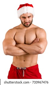 Passionate sexy man in a festive Santa hat isolated on a white background. Christmas fitness concept.