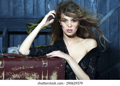 Passionate sexy young woman in black lace blouse standing near old fashioned aged brown suitcase in garage on grey wooden wall background, horizontal picture