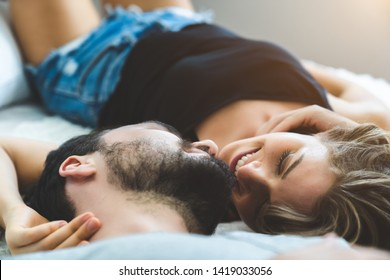 Passionate woman gently kissing man on with romantic kiss.desire lying on bed.
