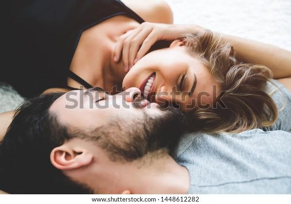情熱的な女性は、男性に優しく接吻し、ロマンチックなキスをします。ベッドの上に寝た欲望。