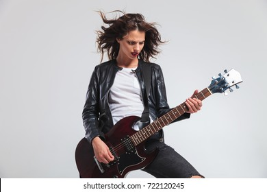 passionate woman guitarist with flying hair playing rock and roll music on her electric guitar
