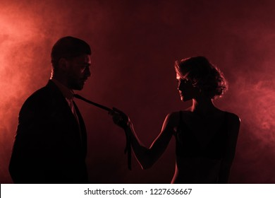 passionate woman and man in smoke on red background