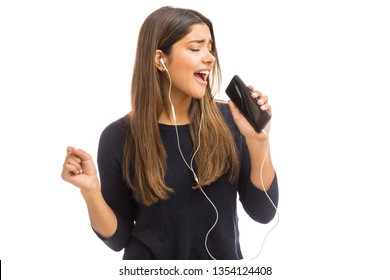 Passionate woman wearing headphones while singing into her cell phone in white studio