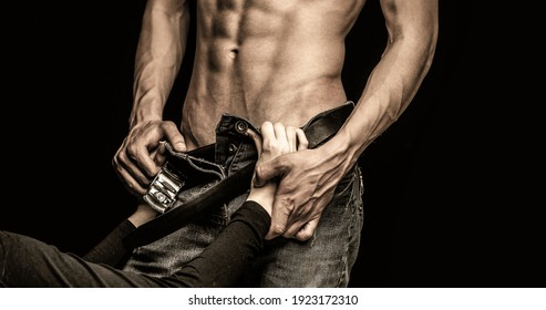Passionate young couple on dark background. Sensual touch. Sensual girl. Sexual abuse. Female hand unfolds mens zipper on jeans. Brutal sex. Sexy woman roztebat man pants. Copy space