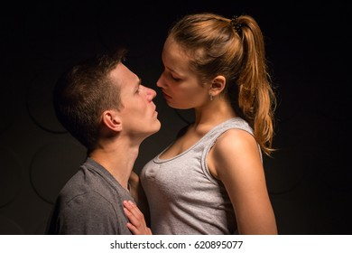 Passionate young couple in the room and the darkness around