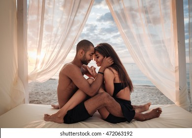 Passionate young couple sitting in bed on the beach