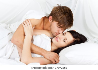 Passionate young lovely couple lying in a bed, intimate kissing happy smile love
