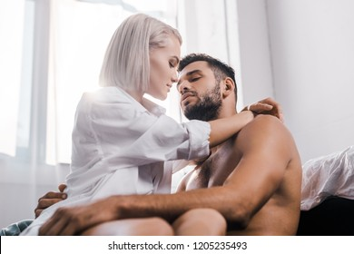 passionate young woman embracing her shirtless boyfriend