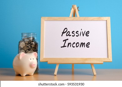Passive Income, financial concept. Mason jar with coins inside, piggy bank and whiteboard on wooden table.