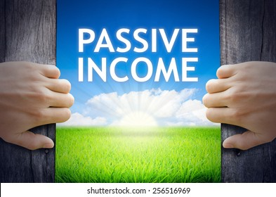 Passive Income. Hand opening an old wooden door and found Passive Income word floating over green field and bright blue Sky Sunrise.