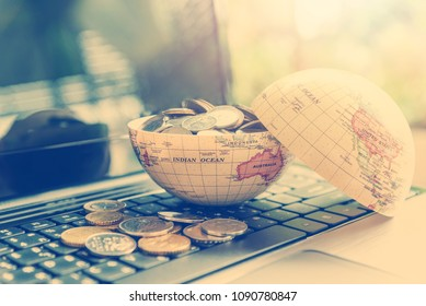 Passive income or making money / wealth from online ecommerce concept : Open globe filled with coins on a laptop, depicts new entrepreneur in new era gain more revenue or income from internet sales.