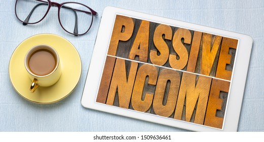 passive income word abstract in letterpress wood type on a digital tablet  - business financial flat lay concept