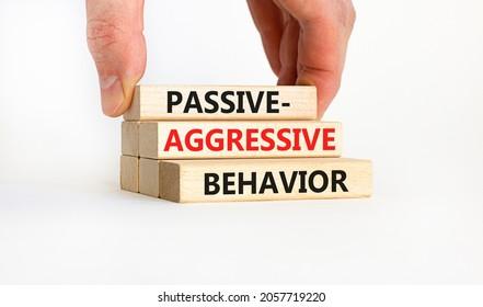 Passive-aggressive behavior symbol. Concept words Passive-aggressive behavior on wooden blocks. Businessman hand. Beautiful white background. Business, Passive-aggressive behavior concept. Copy space.