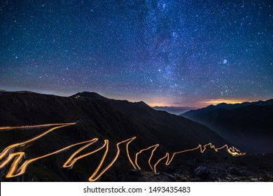 Passo dello Stelvio - Stelvio pass in Italy, Ortler Alps, Italy - curvy road through mountains at night with starry sky