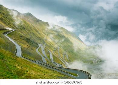 Passo dello Stelvio. Serpentine mountain road in Italy. Foggy weather, very cloudy. Rainbow.