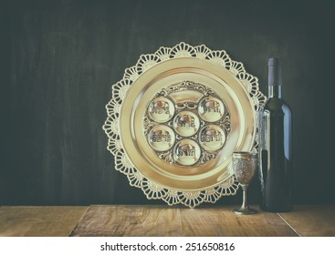 passover background (jewish holiday). traditional seder plate and wine over wooden board. retro filtered image