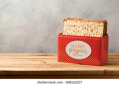 Passover celebration concept with matzoh on wooden table over bright background with copy space