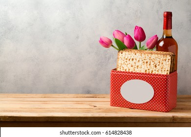 Passover celebration concept with matzoh, wine and tulip flowers over bright background with copy space