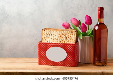 Passover celebration concept with wine bottle, matzoh and tulip flowers over bright background