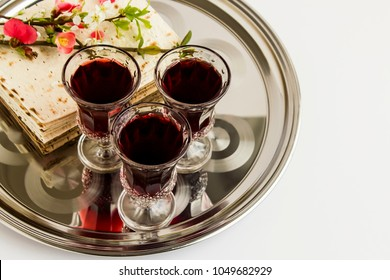 Passover, the Feast of Unleavened Bread,matzah bread and red wine glasses on the shinny round metal tray.Close up taken,isolated.
