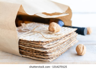 Passover grocery shopping composition with a matzah or matza and red kosher wine in a paper shopping bag.