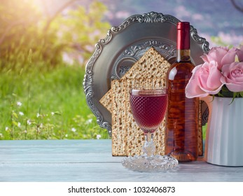 Passover holiday celebration concept with wine, matzo, flowers and seder plate over green grass background