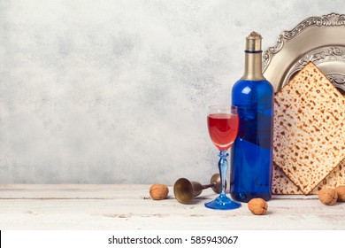Passover holiday concept with blue wine bottle and matzoh over rustic background with copy space