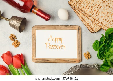 Passover holiday concept seder plate, matzoh and photo frame on bright background. Top view from above