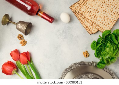 Passover holiday concept seder plate, matzoh and wine bottle on bright background. Top view from above