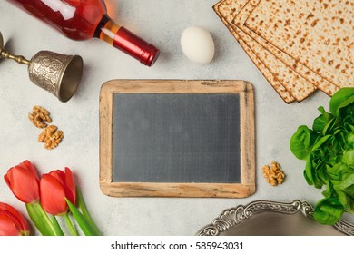 Passover holiday concept seder plate, matzoh and chalkboard on bright background. Top view from above