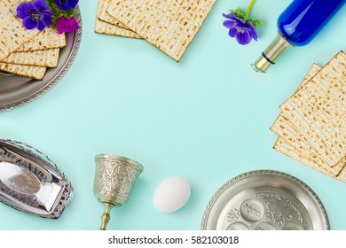 Passover holiday concept with wine bottle, matzoh and spring flowers over mint background with copy space. Top view from above