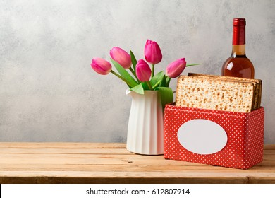 Passover holiday concept with wine bottle, matzoh and tulip flowers over bright background