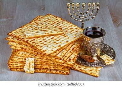 passover matzo (jewish passover bread) with kiddush cup of wine on wooden table