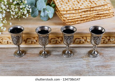 Passover matzoh jewish holiday bread, four glasses kosher wine over wooden table.